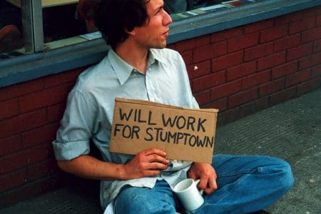 "Raymond holding a signs that says ""WILL WORK FOR STUMPTOWN"" - part of an early art project."